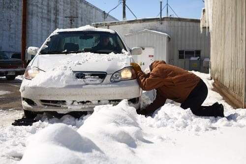 Arne Pinto places one of his patented GoTreads underneath the tires of a car stuck in a snowbank as part of a demonstration on Friday. (Aaron Marineau/The Hutchinson News)